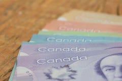 καναδικό νόμισμα Δολάρια Κλείστε επάνω των λογαριασμών μετρητών στον αγροτικό ξύλινο πίνακα