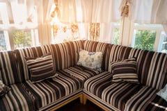 Καναπές γωνιών κοντά στα παράθυρα Στοκ φωτογραφίες με δικαίωμα ελεύθερης χρήσης