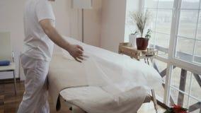 Καναπές κάλυψης γιατρών με το μίας χρήσης φύλλο σε σε αργή κίνηση απόθεμα βίντεο