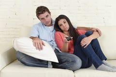 Καναπές τηλεοπτικών μαζί στο σπίτι καναπέδων προσοχής ζεύγους που φαίνεται τρυπημένα ματαιωμένα μεταστρέφοντας κανάλια Στοκ εικόνα με δικαίωμα ελεύθερης χρήσης
