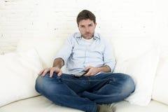 Καναπές τηλεοπτικών στο σπίτι καθιστικών προσοχής ατόμων με τον τηλεχειρισμό που φαίνεται πολύ ενδιαφερόμενο Στοκ Εικόνα