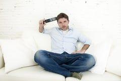 Καναπές τηλεοπτικών στο σπίτι καθιστικών προσοχής ατόμων με τον τηλεχειρισμό που φαίνεται πολύ ενδιαφερόμενο Στοκ φωτογραφίες με δικαίωμα ελεύθερης χρήσης