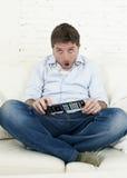 Καναπές τηλεοπτικών στο σπίτι καθιστικών προσοχής ατόμων με τον τηλεχειρισμό που φαίνεται πολύ ενδιαφερόμενο Στοκ φωτογραφία με δικαίωμα ελεύθερης χρήσης