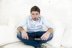 Καναπές τηλεοπτικών στο σπίτι καθιστικών προσοχής ατόμων με τον τηλεχειρισμό που φαίνεται πολύ ενδιαφερόμενο Στοκ εικόνα με δικαίωμα ελεύθερης χρήσης