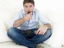 Καναπές τηλεοπτικών στο σπίτι καθιστικών προσοχής ατόμων με τον τηλεχειρισμό που φαίνεται πολύ ενδιαφερόμενο Στοκ Εικόνες