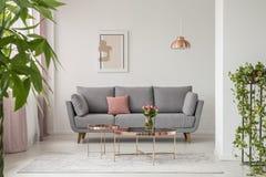 Καναπές Comfy, τραπεζάκι σαλονιού χαλκού και εγκαταστάσεις σε ένα φωτεινό εσωτερικό καθιστικών στοκ εικόνες