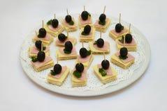 Καναπεδάκια με τις παστωμένες ελιές, το τεμαχισμένα τυρί και το ζαμπόν στο άσπρο πιάτο στοκ φωτογραφίες με δικαίωμα ελεύθερης χρήσης