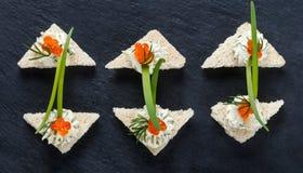 Καναπεδάκια ορεκτικών με το κόκκινο τυρί χαβιαριών και κρέμας στενό σε επάνω υποβάθρου πλακών πετρών στοκ εικόνες