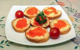 Καναπεδάκια με το κόκκινο χαβιάρι στο άσπρο πιάτο Στοκ Εικόνες