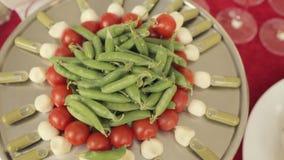 Καναπεδάκια στα μεγάλα δίσκων από τις ντομάτες, μοτσαρέλα και σάλτσα, στο κέντρο των λοβών μπιζελιών δίσκων απόθεμα βίντεο
