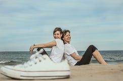 Κανονικές γυναίκες στην παραλία που χαμογελά και που κάθεται στην άμμο Στοκ Εικόνες