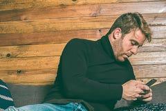 Κανονικός τύπος που εξετάζει το τηλέφωνο κυττάρων στον καναπέ Ντυμένος στα περιστασιακά ενδύματα Ένας νέος, ξένοιαστος τρόπος ζωή Στοκ Εικόνα