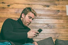Κανονικός τύπος που εξετάζει το τηλέφωνο κυττάρων στον καναπέ Ντυμένος στα περιστασιακά ενδύματα Ένας νέος, ξένοιαστος τρόπος ζωή Στοκ φωτογραφία με δικαίωμα ελεύθερης χρήσης