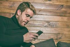 Κανονικός τύπος που εξετάζει το τηλέφωνο κυττάρων στον καναπέ Ντυμένος στα περιστασιακά ενδύματα Ένας νέος, ξένοιαστος τρόπος ζωή Στοκ Εικόνες