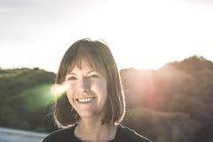 Κανονικό χαμόγελο κοριτσιών brunette Γυναίκα με ένα χαμόγελο σε ένα ηλιοβασίλεμα Στοκ φωτογραφίες με δικαίωμα ελεύθερης χρήσης