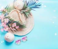 Καπέλο αχύρου γυναικών με τα γυαλιά ηλίου, τα φύλλα φοινικών και τα ποτά καρύδων στο μπλε υπόβαθρο, τοπ άποψη τροπικές διακοπές έ στοκ φωτογραφίες