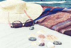 Καπέλο αχύρου, κάλυψη-επάνω στα beachwear γυαλιά περικαλυμμάτων και ήλιων σε μια τροπική παραλία στοκ εικόνες με δικαίωμα ελεύθερης χρήσης