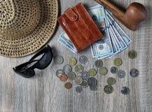 Καπέλο αχύρου, κόκκινο πορτοφόλι με τα αμερικανικά δολάρια, τα διάφορα ξένα νομίσματα και τα γυαλιά ηλίου στον πίνακα στοκ φωτογραφία με δικαίωμα ελεύθερης χρήσης