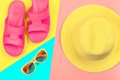 Καπέλο, γυαλιά ηλίου και παντόφλες σε ένα υπόβαθρο κρητιδογραφιών τρεις-χρώματος του μπλε, κίτρινος και ρόδινος Στοκ εικόνα με δικαίωμα ελεύθερης χρήσης