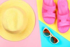 Καπέλο, γυαλιά ηλίου και παντόφλες σε ένα υπόβαθρο κρητιδογραφιών τρεις-χρώματος του μπλε, κίτρινος και ρόδινος Στοκ φωτογραφία με δικαίωμα ελεύθερης χρήσης