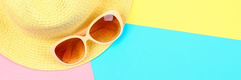 Καπέλο, γυαλιά ηλίου σε ένα υπόβαθρο κρητιδογραφιών τρεις-χρώματος του μπλε, κίτρινος και ρόδινος Στοκ φωτογραφία με δικαίωμα ελεύθερης χρήσης