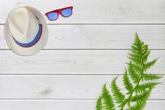 Καπέλο θερινών εξαρτημάτων, γυαλιά ηλίου στο άσπρο ξύλινο υπόβαθρο το ελάχιστο επίπεδο βάζει την έννοια από το ταξίδι καλοκαιριού στοκ φωτογραφία