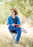 Καπέλο και ανάγνωση ένδυσης γυναικών το βιβλίο στην καρέκλα Στοκ Εικόνες