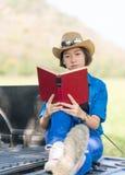 Καπέλο και ανάγνωση ένδυσης γυναικών το βιβλίο στο ανοιχτό φορτηγό Στοκ φωτογραφίες με δικαίωμα ελεύθερης χρήσης