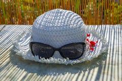 Καπέλο και γυαλιά ηλίου γυναικών ` s στον πίνακα Θερινή ανασκόπηση Φως του ήλιου μέσω του φράκτη Στοκ Εικόνα