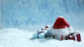 Καπέλο και δώρα Santa στο χιόνι απόθεμα βίντεο