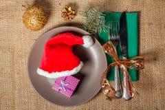 Καπέλο και παρόν Χριστουγέννων κόκκινο στο κιβώτιο δώρων στο πιάτο, το μαχαίρι και τα FO Στοκ Φωτογραφίες