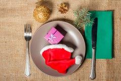 Καπέλο και παρόν Χριστουγέννων κόκκινο στο κιβώτιο δώρων στο πιάτο, το δίκρανο και kni Στοκ Εικόνα