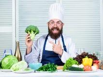 Καπέλο μαγείρων ατόμων και μπρόκολο λαβής ποδιών υγιής διατροφή έννοιας Γενειοφόρος επαγγελματικός αρχιμάγειρας που μαγειρεύει τα στοκ φωτογραφία