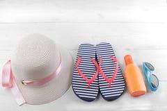 καπέλο με μια ρόδινη κορδέλλα, μια βιετναμέζικη, suntan κρέμα και μπλε γυαλιά ηλίου άσπρος ξύλινος ανασκόπησης στοκ εικόνες με δικαίωμα ελεύθερης χρήσης