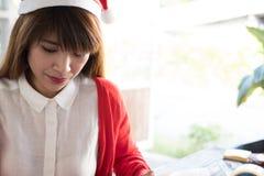 Καπέλο santa ένδυσης γυναικών το ασιατικό θηλυκό πουκάμισο και το κόκκινο ένδυσης άσπρο πλέκουν Στοκ Εικόνα