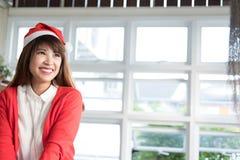 Καπέλο santa ένδυσης γυναικών το ασιατικό θηλυκό πουκάμισο και το κόκκινο ένδυσης άσπρο πλέκουν Στοκ Φωτογραφία