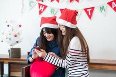 Καπέλο santa ένδυσης φίλων κοριτσιών της Ασίας σε χρησιμοποίηση κομμάτων Χαρούμενα Χριστούγεννας Στοκ Εικόνες