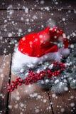Καπέλο Santa, δέντρο γουνών κλάδων και κόκκινα μούρα στο ηλικίας ξύλινο β Στοκ εικόνα με δικαίωμα ελεύθερης χρήσης