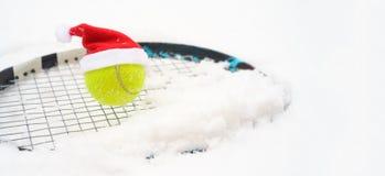 Καπέλο Santa στη σφαίρα αντισφαίρισης στη ρακέτα στο άσπρο χειμερινό υπόβαθρο χιονιού με snowflakes Χαρούμενα Χριστούγεννα και νέ στοκ εικόνα