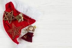 Καπέλο santa Χριστουγέννων με τα χρυσά παιχνίδια αγγέλου αστεριών άσπρο σε αγροτικό Στοκ φωτογραφία με δικαίωμα ελεύθερης χρήσης