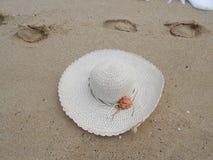 Καπέλο αχύρου και ίχνος στην αμμώδη θάλασσα παραλιών Στοκ Φωτογραφία