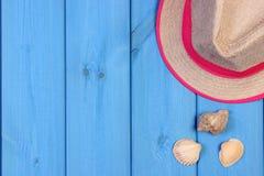 Καπέλο αχύρου και θαλασσινά κοχύλια στους μπλε ξύλινους πίνακες, εξαρτήματα για το καλοκαίρι, διάστημα αντιγράφων για το κείμενο Στοκ εικόνα με δικαίωμα ελεύθερης χρήσης