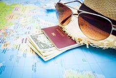 Καπέλο, γυαλιά ηλίου, διαβατήριο, χρήματα και αεροσκάφη στον παγκόσμιο χάρτη Στοκ Εικόνες