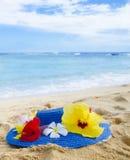 Καπέλο γυναίκας με τα τροπικά λουλούδια στην αμμώδη παραλία Στοκ φωτογραφία με δικαίωμα ελεύθερης χρήσης