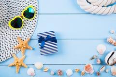Καπέλο και γυαλιά ηλίου με τα κοχύλια, τους αστερίες, το κιβώτιο δώρων και το σχοινί επάνω Στοκ Φωτογραφία
