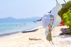 Καπέλο και γυαλιά ηλίου που βρίσκονται στα τροπικά γυαλιά ηλίου παραλιών άμμου στην παραλία Η όμορφη ταπετσαρία άποψης θάλασσας,  Στοκ Εικόνες