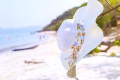 Καπέλο και γυαλιά ηλίου που βρίσκονται στα τροπικά γυαλιά ηλίου παραλιών άμμου στην παραλία Η όμορφη ταπετσαρία άποψης θάλασσας,  Στοκ Φωτογραφία