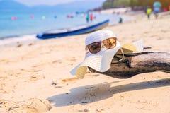 Καπέλο και γυαλιά ηλίου που βρίσκονται στα τροπικά γυαλιά ηλίου παραλιών άμμου στην παραλία Η όμορφη ταπετσαρία άποψης θάλασσας,  Στοκ Εικόνα