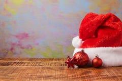 Καπέλο και διακοσμήσεις santa Χριστουγέννων στον ξύλινο πίνακα πέρα από το καλλιτεχνικό υπόβαθρο Στοκ Εικόνα