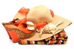 Καπέλο παραλιών, πετσέτα, παπούτσια γυναικών και ένα θαλασσινό κοχύλι Στοκ φωτογραφία με δικαίωμα ελεύθερης χρήσης